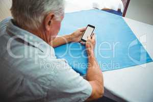 seated retired man looking at his smartphone