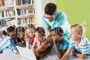 Teacher and kids using laptop in library