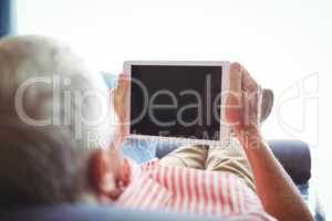 Lying on a couch senior man looking at digital tablet