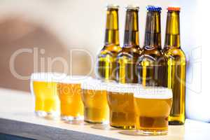 Arranged beer glasses and bottles on the bar counter