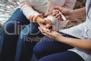Nurse helping senior woman with diabetes