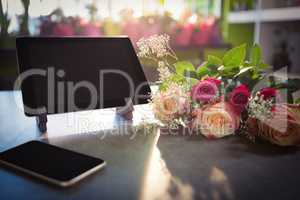 Flower bouquet with smartphone and digital tablet on the table