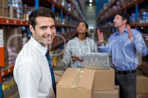 Focus of manager holding cardboard box and smiling in front of w
