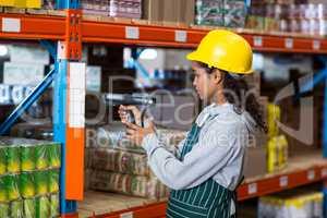 Female worker wearing yellow helmet scanning documents