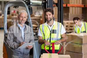 Worker and manager are smiling and posing during work