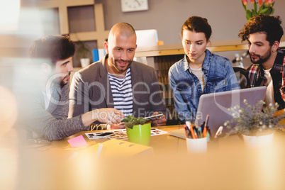 Graphic designer using digital tablet with his coworker