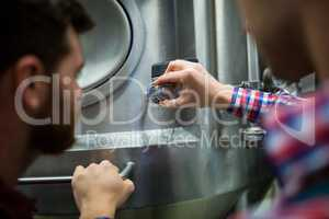 Maintenance workers examining brewery machine