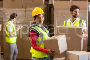 Focus of worker is holding goods and smiling to the camera