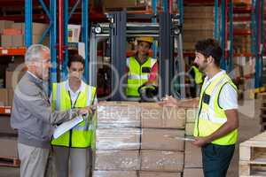 View of manager is talking with worker about goods