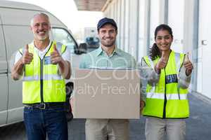 Portrait of workers are posing with thumbs up close to a deliver