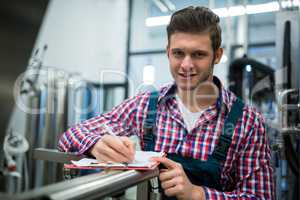Maintenance worker writing on clipboard