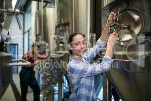 Female maintenance worker examining brewery machine