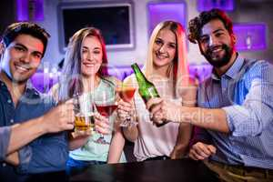 Group of friends toasting cocktail, beer bottle and beer glass a