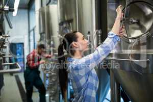 Female maintenance worker examining brewery machine