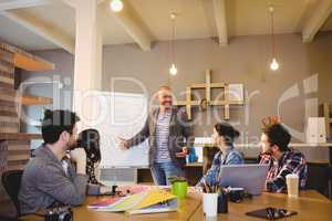 Male graphic designer discussing chart on white board with cowor
