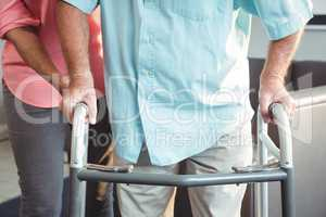 Senior woman helping senior with walking aid