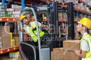 Focus of worker sitting on a pallet truck is pointing shelves