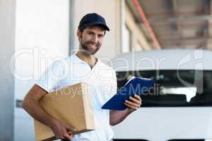 Delivery man is holding a cardboard box and a clipboard and posi