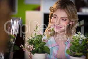 Happy female florist looking at flower pot