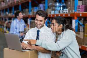 smiling workers pointing at laptop