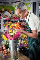 Male florist watering flowers with watering can