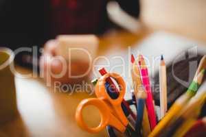 Color pencils and scissor in pen holder