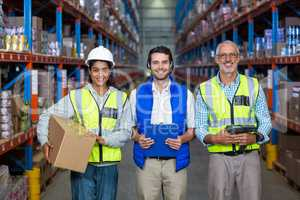 Warehouse workers looking at camera in warehouse