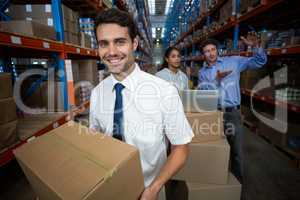 Focus of manager holding cardboard box and smiling