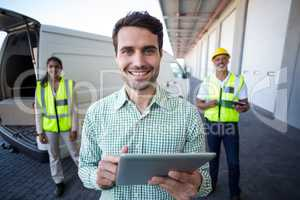 Focus of manager is holding a tablet in front of his colleagues