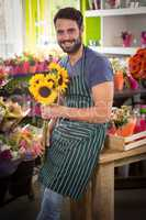 Male florist holding bunch of flowers at his flower shop