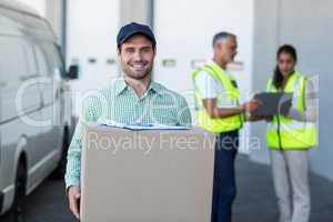 Focus of delivery man is holding a cardboard box and smiling to