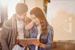 Graphic designer with his coworker looking at digital tablet