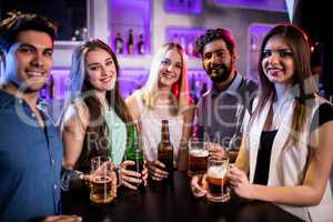 Group of friends holding beer bottle and beer glass at bar count