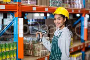 Female warehouse worker using digital equipment