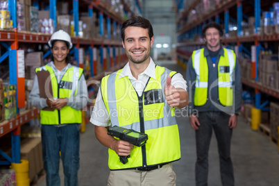 Worker with thumb up wearing yellow safety vest