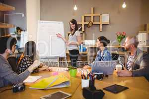 Female graphic designer discussing chart on white board with cow