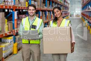 Happy workers are holding laptop and cardboard box and posing