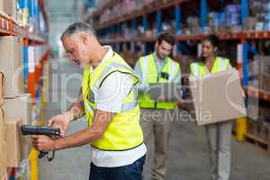 Focus of worker is working on cardboard boxes with his colleague