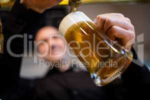 Brewer filling beer in beer glass from beer pump