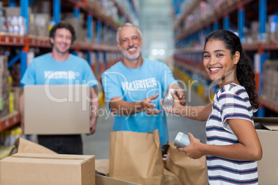 Focus of happy woman gives some goods to volunteers