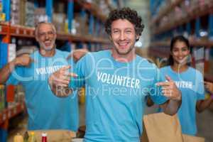 Focus of happy volunteer showing his tee-shirt in front of his t