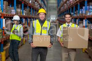 Workers looking at camera while holding box
