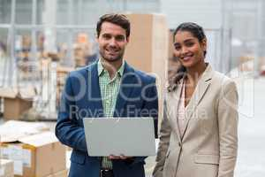 Portrait of happy managers are posing and smiling with a laptop