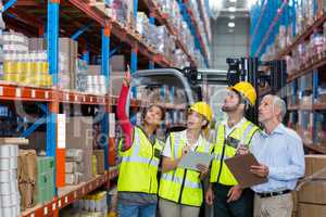 Worker showing shelves to her colleagues and manager