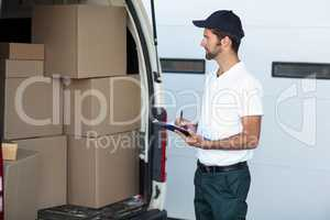 Delivery man is looking his goods and holding a clipboard