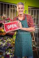 Male florist holding open signboard at flower shop