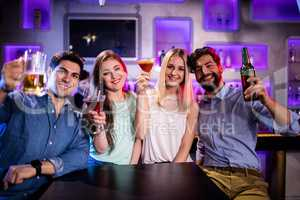 Group of friends showing cocktail, beer bottle and beer glass at