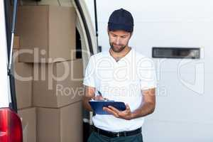 Delivery man is writing on clipboard next to his van