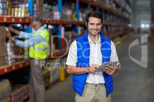 Standing worker smiling at camera while holding digital tablet