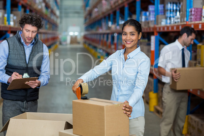 Focus of manager is smiling and posing during work with his coll